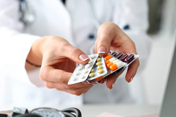 Doctor holding various medications.