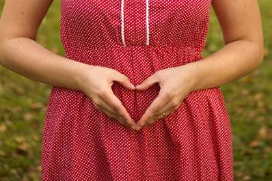 Woman during first trimester of pregnancy, hands in shape of heart over stomach.