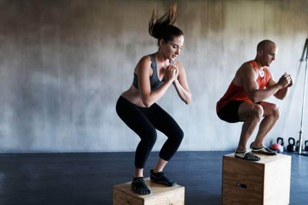 woman and man doing box jumps