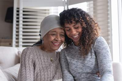 mother with cancer leaning on daughter, both smiling