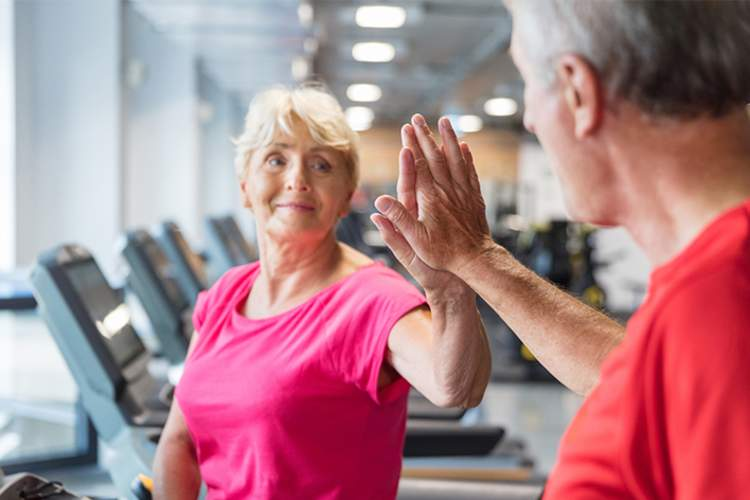 Couple high-five while exercising at the gym.