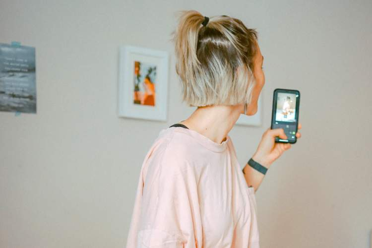 woman in big t-shirt looking at phone