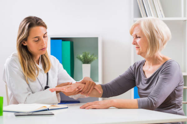 Woman talking to doctor about joint pain.