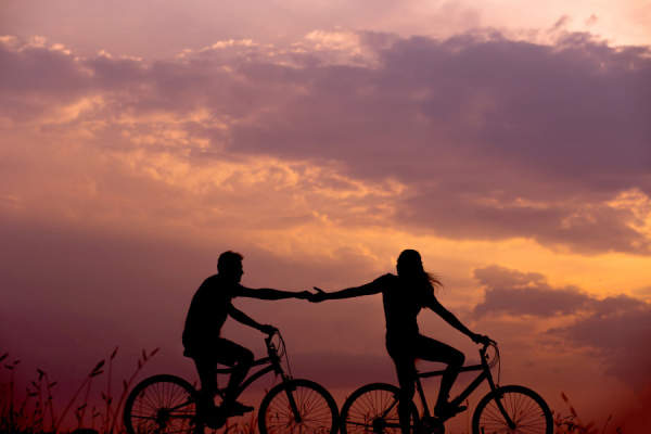 couple on bikes touching hands