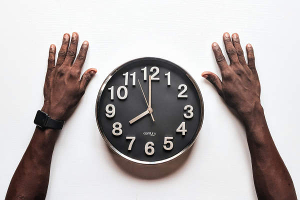 arms on table surrounding clock
