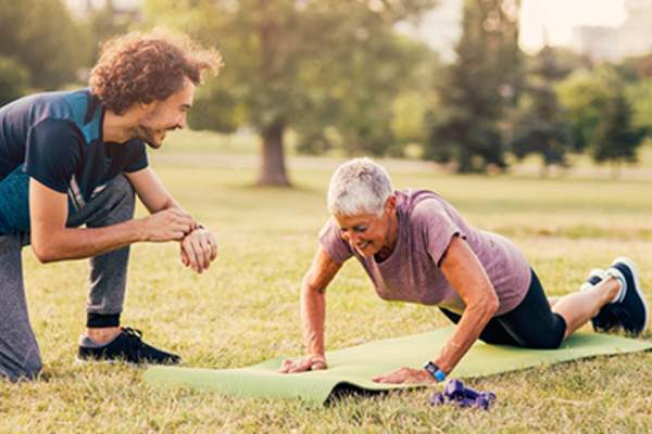 Senior woman working with a personal trainer and doing push ups outdoors.