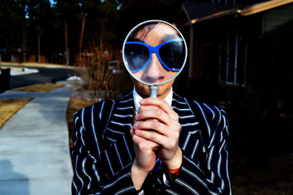 man holding magnifying glass up to face