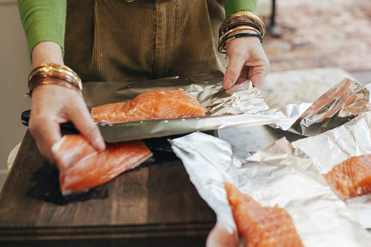 Woman wrapping salmon in foil.