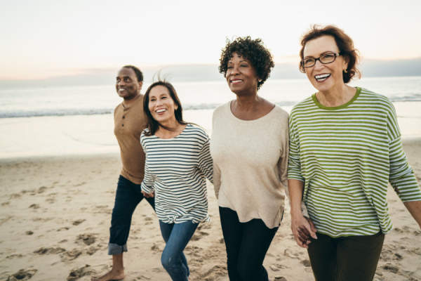 group of senior women walking on the beach