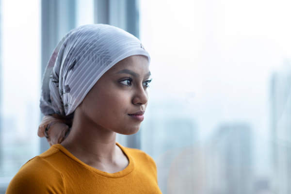 Woman with scarf on her head looking out window