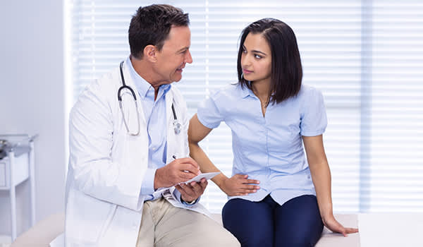 GI specialist seeing young woman patient image.