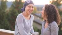 woman fighting cancer and wearing a head wrap talks with her sister on a porch
