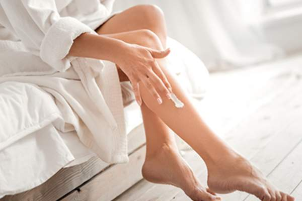 Woman applying lotion to her leg.