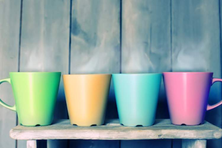 Multicolored mugs on a shelf.