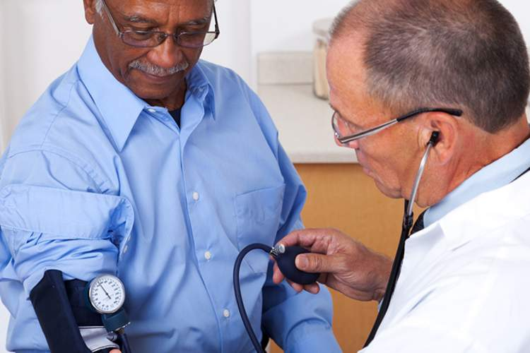 Doctor taking older man's blood pressure in office.