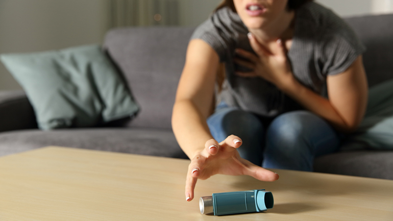 Woman reaching for an inhaler.
