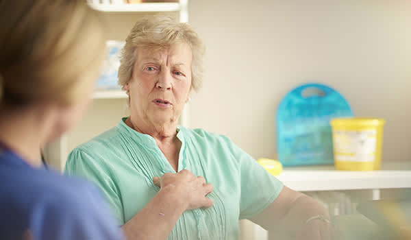 Senior woman discussing chest pain with a doctor.