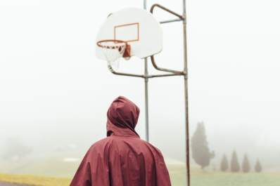 Person wearing raincoat standing in front of basketball hoop