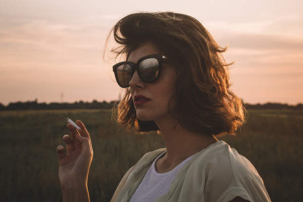 woman in sunglasses smoking
