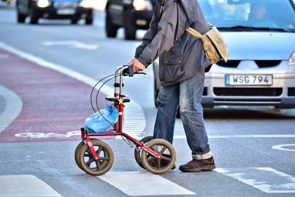man crossing street using rollator