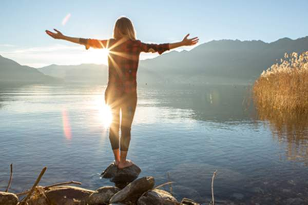 Woman standing on rock with outreached arms near beautiful mountain lake.