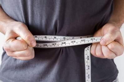 Man measuring his waist size with a tape measure.