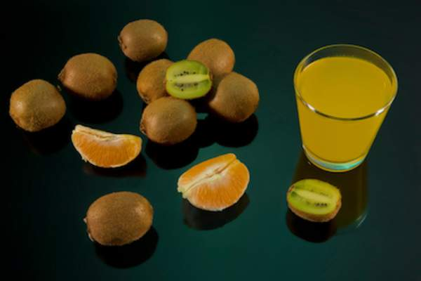 Orange and kiwis on black background with glass of kiwi-orange juice.