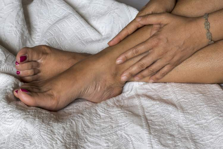 A woman sits in bed with restless legs syndrome.