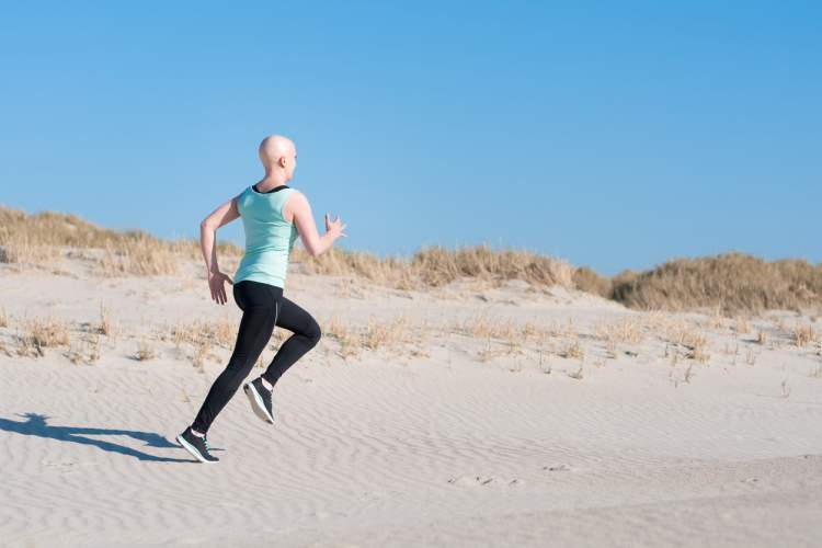 Woman jogging on the beach during her cancer treatment.