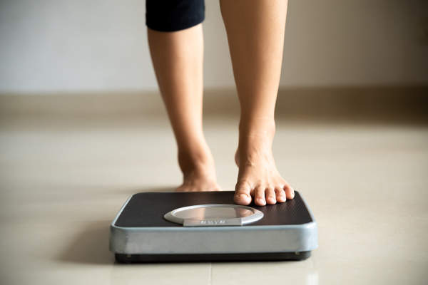 Woman stepping onto a scale to weight herself