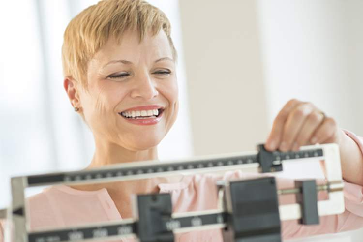 A happy woman smiles while weighing herself on a scale.