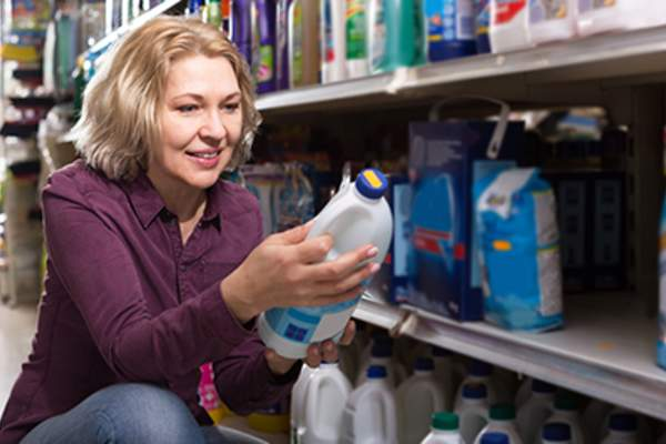 Woman shopping for bleach in a store.