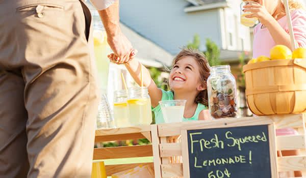 Children selling lemonade at a lemonade stand in the summer