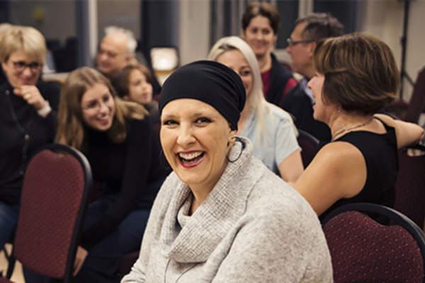 Smiling woman surrounded by supportive cancer community.
