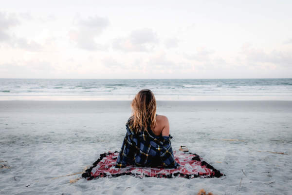woman sitting alone on beach looking at ocean