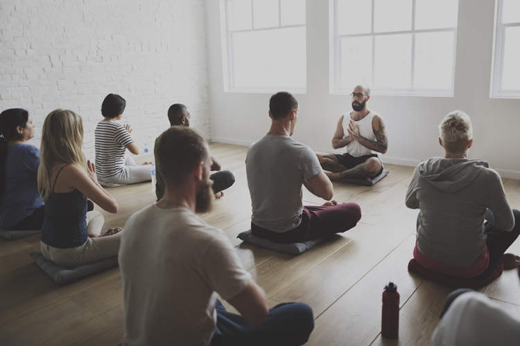 Instructor leading a mindfulness class in a meditation exercise