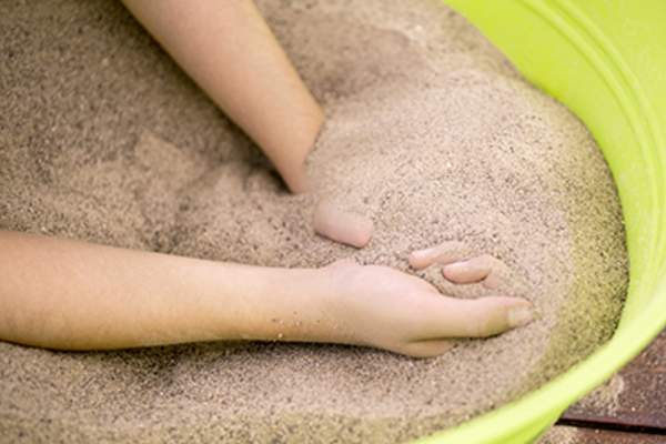 Closeup of hands enjoying and playing with sand in a bucket on a picnic table.