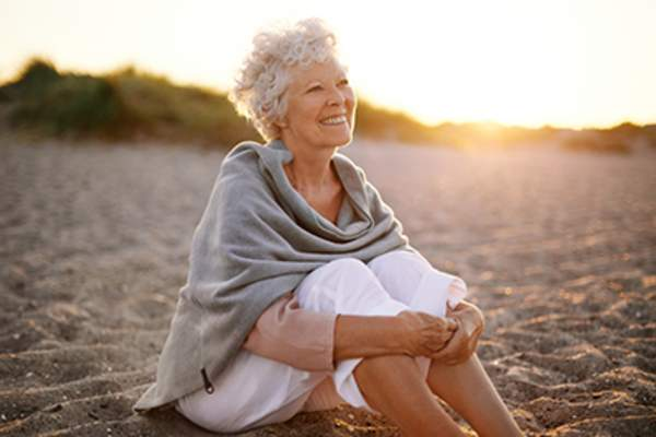 Cheerful senior woman sitting on the beach.