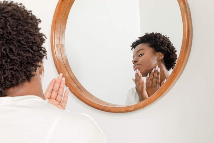 woman putting on cream looking in mirror