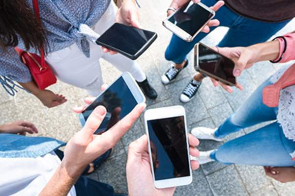 Group of people holding smartphones.