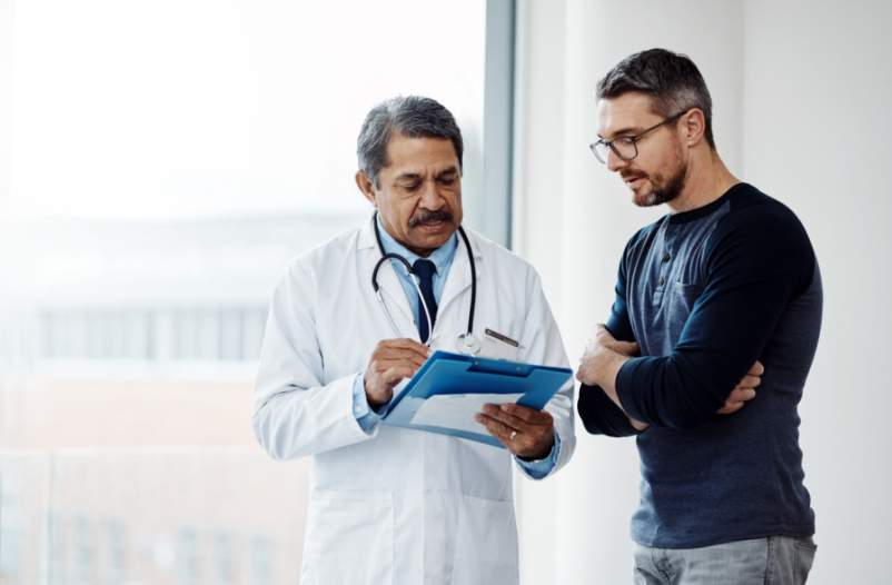 man and doctor talking and looking at chart