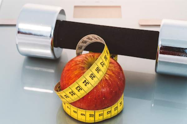 Apple with measuring tape, weight and a scale: weight loss concept.