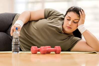 Overweight woman resting during exercise with weights.