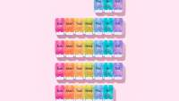 colorful monthly pill containers on pink background