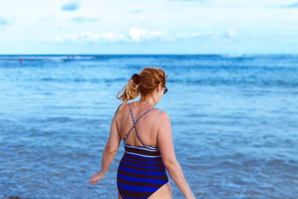 middle aged woman in bathing suit walking into ocean