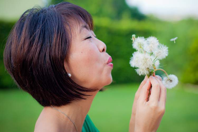 senior woman blowing seeds off of dandelion