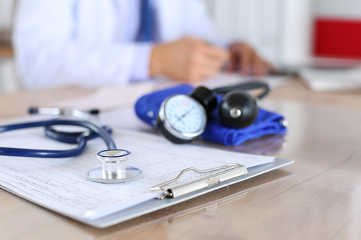 doctor vising blood pressure cuff and stethoscope image