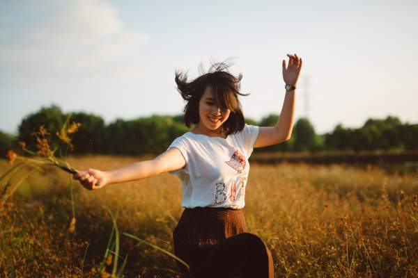 Girl dancing happily in field