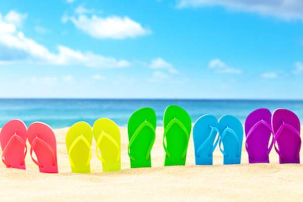 Brightly colored flip flops stuck in sand.