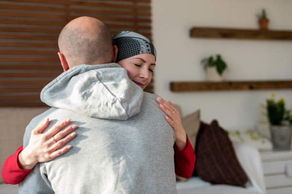 Young adult female cancer patient hugging her husband